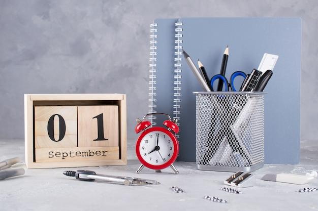 Деревянный календарь, группа школьных принадлежностей, красный будильник на сером столе