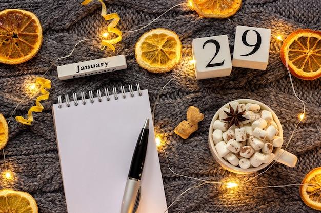 木製カレンダー1月マシュマロとココアのカップ、空の開いたメモ帳