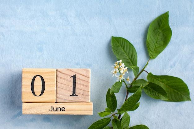 白い花と青い表面に木製のカレンダー6月1日