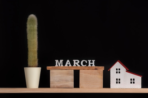 Wooden calendar of march, cactus and house model on black background. copy space.