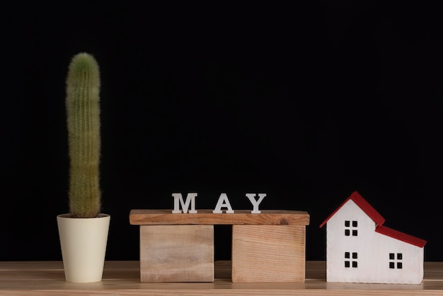 Wooden calendar of may, cactus and house model on black background. copy space.