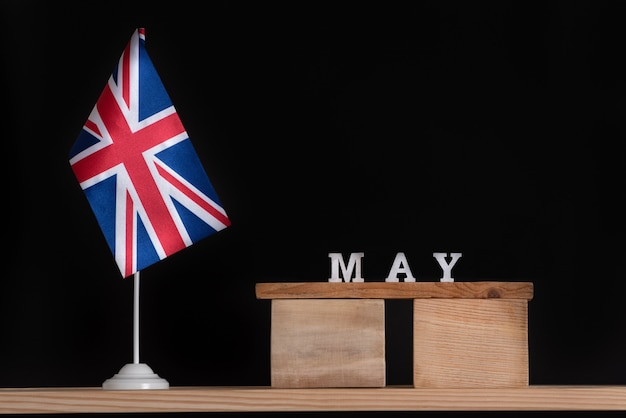 Wooden calendar of may with great britain flag on black space.