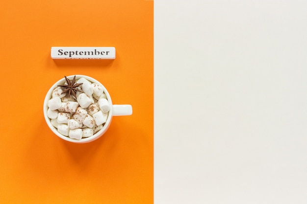 Wooden calendar month september and cup of cocoa with marshmallows on orange beige background