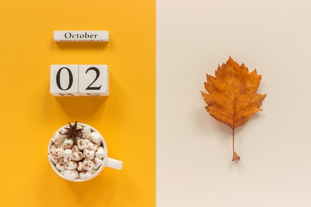 Wooden calendar october 2, cup of cocoa with marshmallows and yellow autumn leaves on yellow beige background.