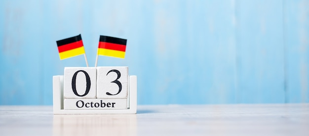 Wooden calendar of october 3rd with miniature germany flags.