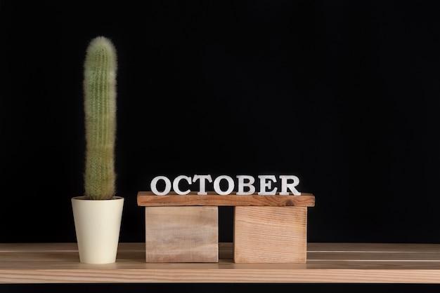 Wooden calendar of october and cactus on black background. mock up.