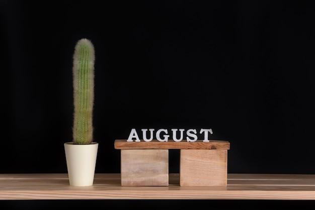 8月の木製カレンダーと黒の背景にサボテン。モックアップ。