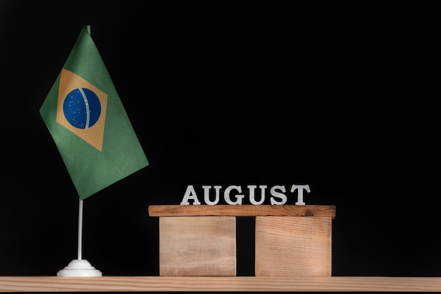 黒の背景にブラジルの旗と8月の木製カレンダー。 8月のブラジルの日付。