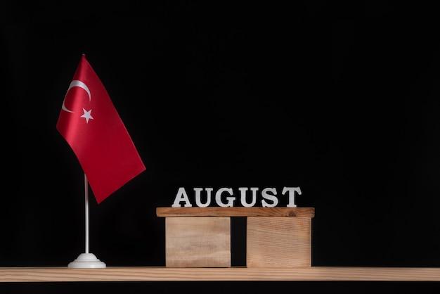 黒の背景にトルコの旗と8月の木製カレンダー。 8月のトルコの休日。