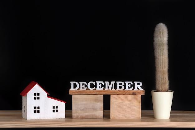 12月の木製カレンダー、黒の背景にサボテンと家のモデル。スペースをコピーします。