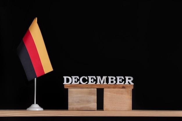 黒の背景にドイツの旗と12月の木製カレンダー。 12月のドイツの休日。