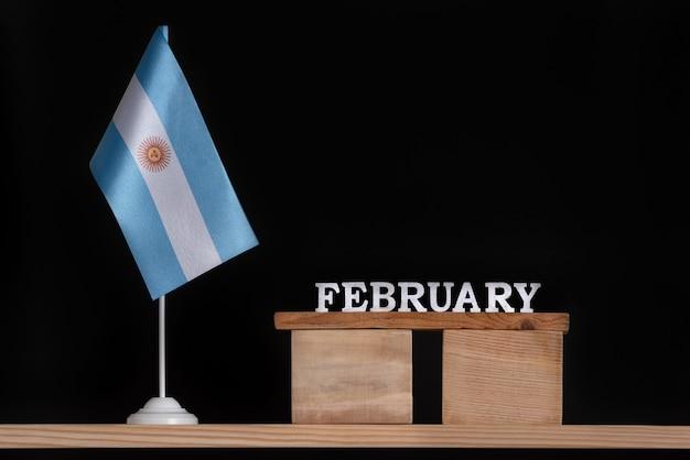 黒の背景にアルゼンチンの旗と2月の木製カレンダー。 2月のアルゼンチンの休日。