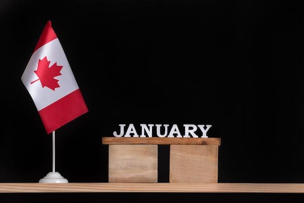 黒いスペースにカナダの旗が付いている1月の木のカレンダー。 1月のカナダの祝日。