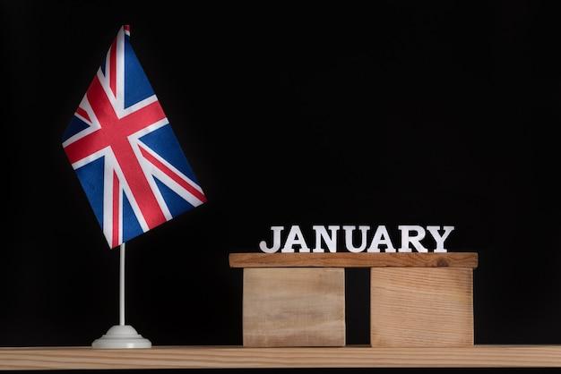 黒の背景にイギリスの旗と1月の木製カレンダー。 1月の英国の休日。