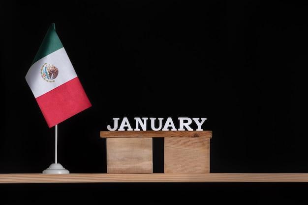 黒い表面にメキシコの旗が付いた1月の木製カレンダー。 1月のメキシコの休日。