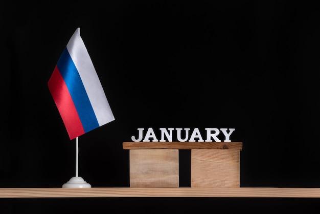 黒いスペースにロシア国旗が付いた1月の木製カレンダー。 1月のロシアでの日付。