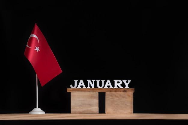 黒い壁にテーブルトルコ国旗と1月の木製カレンダー