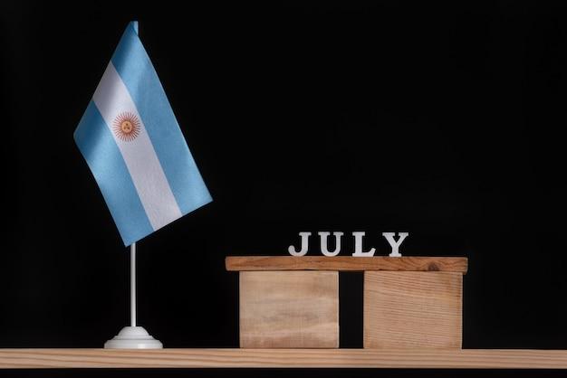 Деревянный календарь июля с аргентинским флагом на черном фоне. праздники аргентины в джуле.