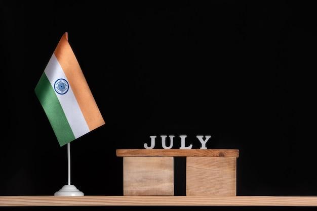 黒の背景にインドの旗と7月の木製カレンダー。 7月のインドの休日。