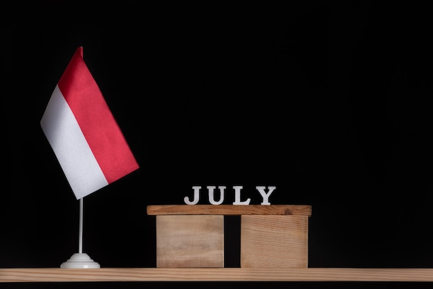 黒の背景にポーランドの旗と7月の木製カレンダー。 7月のポーランドの休日。