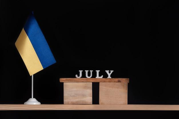 黒の背景にウクライナの旗と7月の木製カレンダー。 7月のウクライナでの日付。
