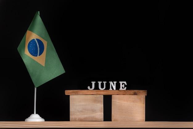 黒の背景にブラジルの国旗と6月の木製カレンダー。 6月のブラジルの日付。