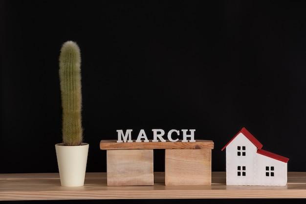 3月の木製カレンダー、黒の背景にサボテンと家のモデル。スペースをコピーします。