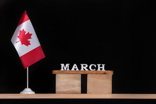 黒の背景にカナダの旗と3月の木製カレンダー。 3月のカナダの祝日。
