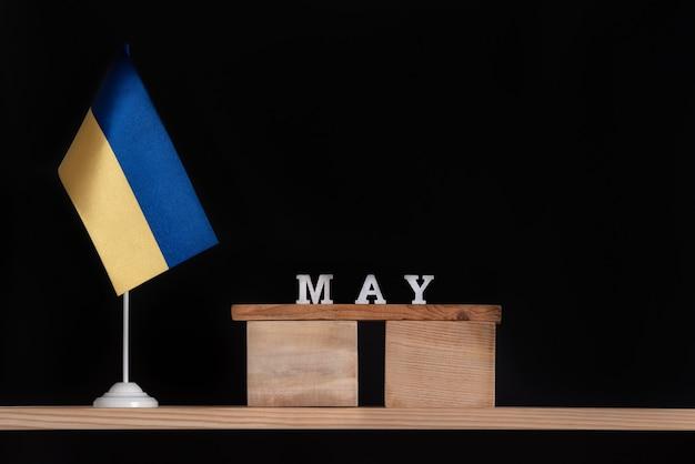 黒の背景にウクライナの旗と5月の木製カレンダー。 5月のウクライナでの日付。