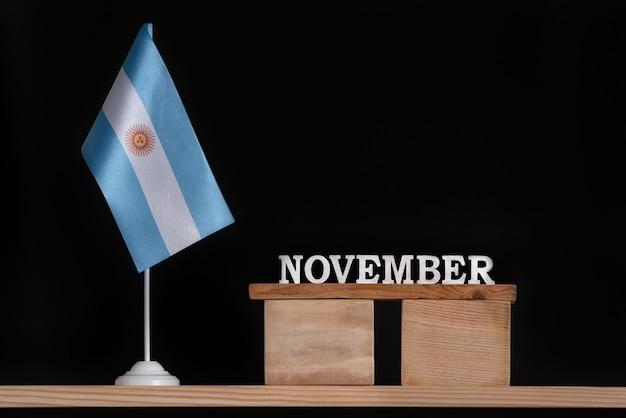黒の背景にアルゼンチンの旗と11月の木製カレンダー。 11月のアルゼンチンの日付。