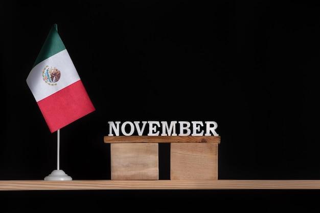 黒の背景にメキシコの旗と11月の木製カレンダー。 11月のメキシコの休日。