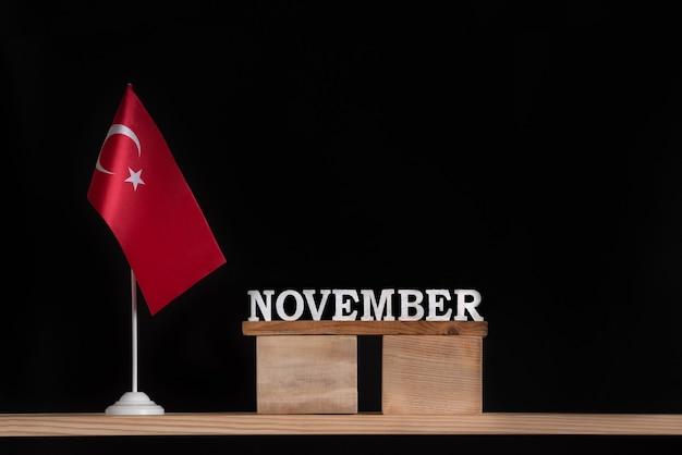 黒の背景にトルコの旗と11月の木製カレンダー。 11月のトルコの休日。