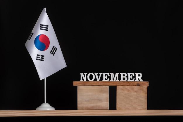 黒の背景に韓国の旗と11月の木製カレンダー。 11月の韓国の休日。