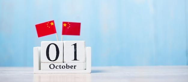 10月1日の木製カレンダー、ミニチュア中国の旗。