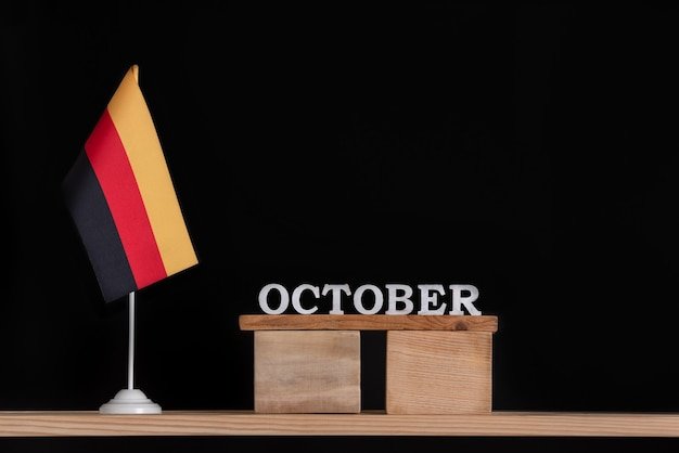 黒の背景にドイツの旗と10月の木製カレンダー。 10月のドイツでの日付。