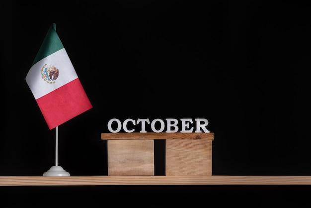 黒の背景にメキシコの旗と10月の木製カレンダー。 10月のメキシコの休日。
