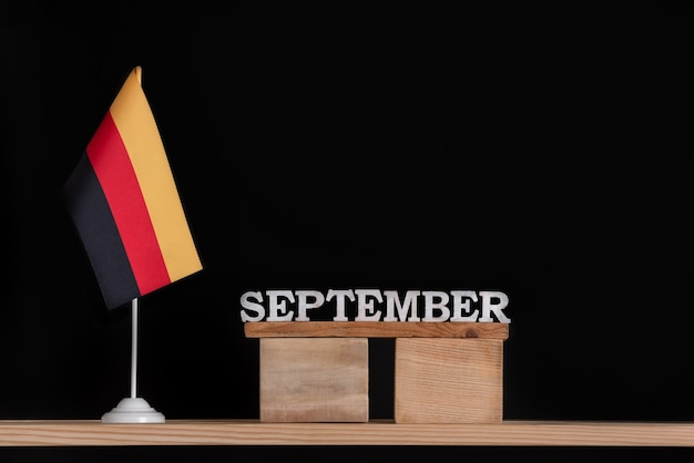 黒の背景にドイツの旗と9月の木製カレンダー。 9月のドイツでの日付。