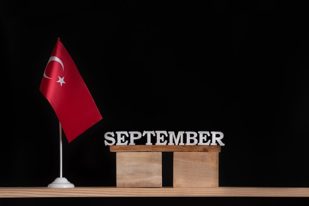 黒の背景にトルコの旗と9月の木製カレンダー。 9月のトルコの休日。