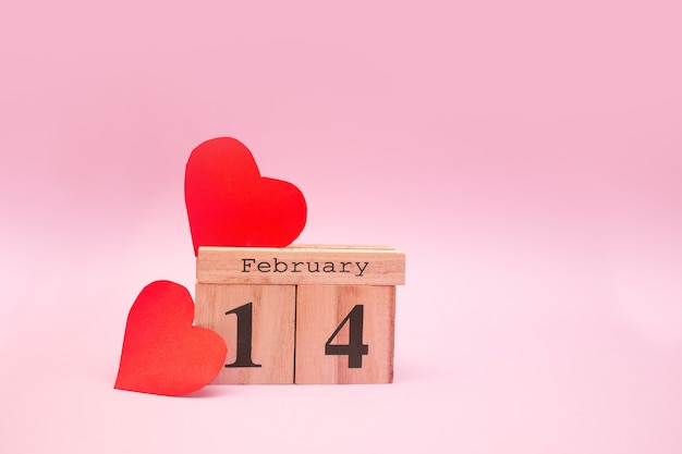 Wooden calendar on a pink background with red hearts. valentine's day february 14