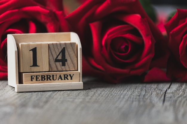 Wooden calendar placed on a gray wooden floor and red rose, valentine's day theme