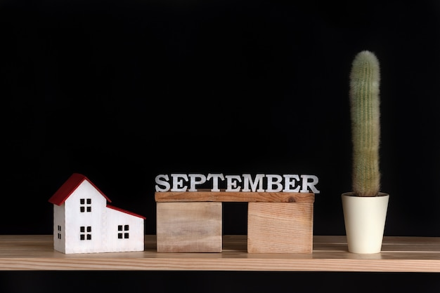 Wooden calendar of september, cactus and house model on black background. copy space.