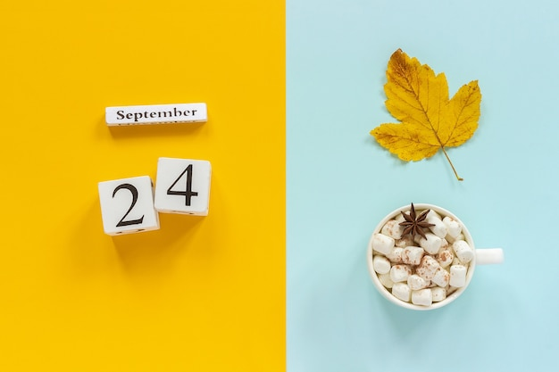 Wooden calendar september, cup of cocoa with marshmallows and yellow autumn leaves on yellow blue