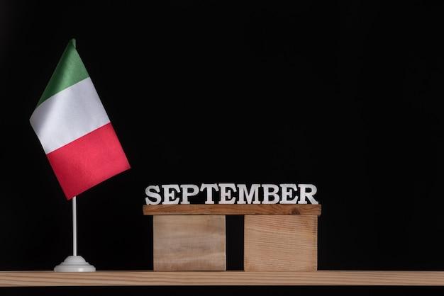 Wooden calendar of september with italian flag on black background. dates in italy in september.