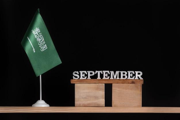 Wooden calendar of september with saudi arabia flag on black. dates of saudi arabia in september.
