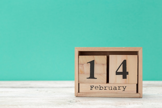 Wooden calendar show of february 14 on wooden tabletop