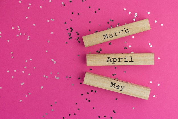 Wooden calendar spring months march, april, may. pink background with multicolored confetti. flat lay style