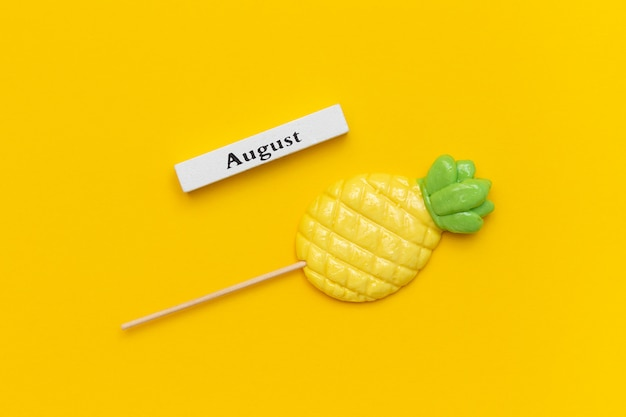 Wooden calendar summer month august and pineapple lollipop on stick on yellow background