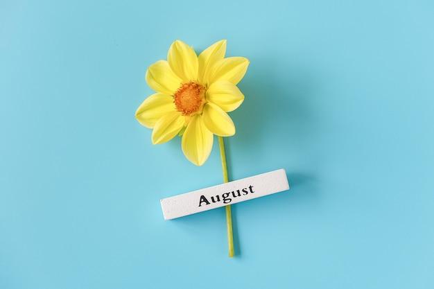8月の木製カレンダー夏の月と青の背景に黄色の花。コピースペース。最小限のスタイル。