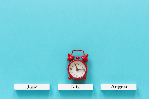 Wooden calendar summer months and red alarm clock over july on blue background.