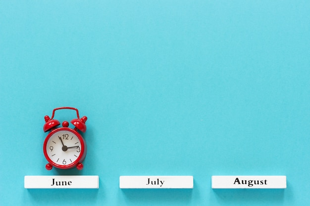Wooden calendar summer months and red alarm clock over june on blue background